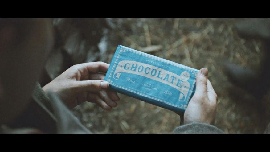 In this handout still image of a television advertisement, released by Sainsbury's on Tuesday, Nov. 18, 2014, an actor dressed dressed as a World War I soldier holds a bar of chocolate. The 40-second mini-movie depicts the 1914 Christmas Truce, when soldiers lay down their arms for a few hours to celebrate the holiday together in no-man's land. (AP Photo/Sainsbury's)