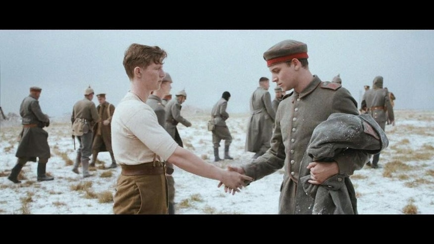 In this handout still image of a television advertisement, released by Sainsbury's on Tuesday, Nov. 18, 2014, an actor dressed as a German WWI soldier, right, and an actor dressed as a British WWI soldier left, shake hands. The 40-second mini-movie depicts the WWI 1914 Christmas Truce, when soldiers lay down their arms for a few hours to celebrate the holiday together in no-man's land. (AP Photo/Sainsbury's)
