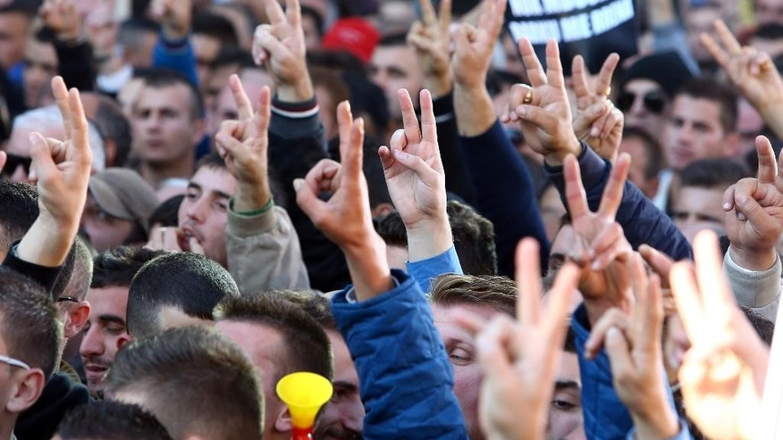 Albanian main opposition Democratic Party supporters make the V-Victory sign during a peaceful rally in Tirana on Saturday, Nov. 22, 2014.  Tens of thousands of Albanians protested against the government's economic policies, claiming they are leading to rising taxes and energy prices and high unemployment. (AP Photo/Hektor Pustina)