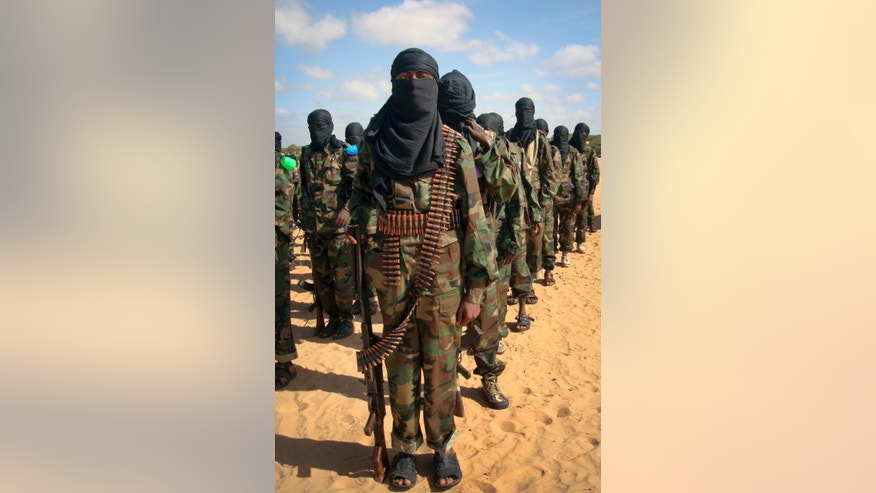 FILE - Armed members of the militant group al-Shabab attend a rally on the outskirts of Mogadishu, Somalia in this Feb. 13, 2012 file photo. Police officials say al-Shabab militants from Somalia have hijacked a bus Saturday Nov. 23, 2014 in northern Kenya and killed 28 non-Muslims on board.  (AP Photo)