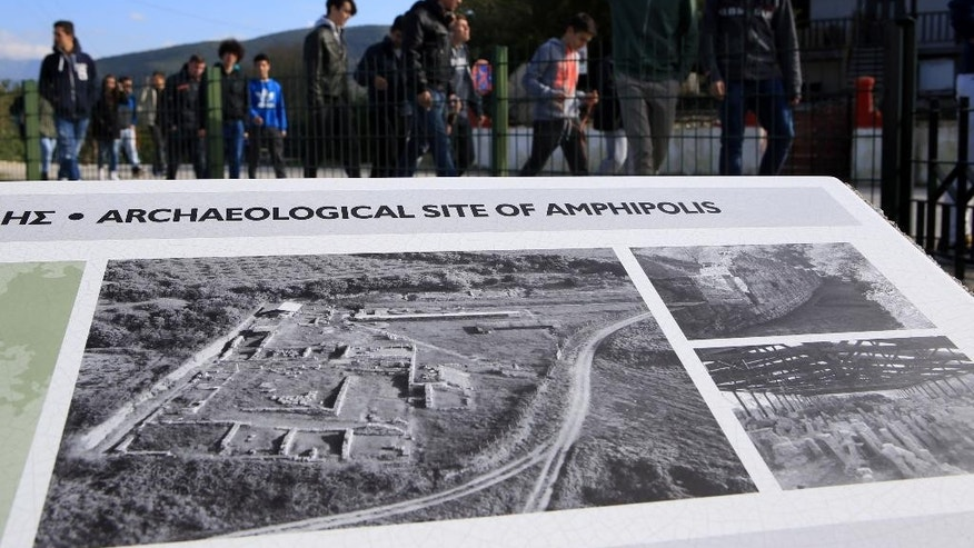 Tourists visit the ancient site of Amphipolis where archaeologists are excavating a large 4th century B.C. tomb, in northern Greece, on Saturday, Nov. 22, 2014. Officials say the vast ancient burial mound at Amphipolis in Greece could contain more than one dead. Greek Culture Minister Costas Tasoulas said Saturday scientists have started the second phase of excavation at the burial site, dating back to Alexander the Great's reign in the late 4th century B.C. (AP Photo/Grigoris Siamidis)