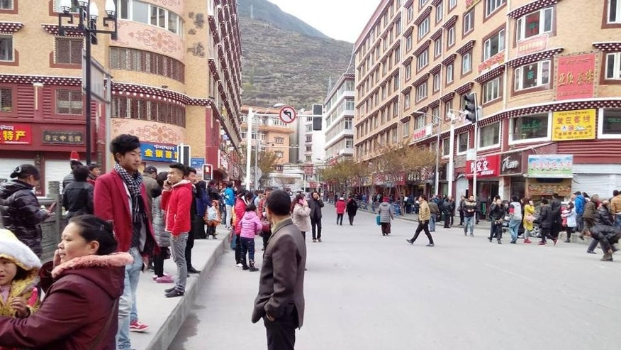 In this photo released by China's Xinhua News Agency, locals stand outside after a quake hit Kangding County in Sichuan Province, China Saturday, Nov. 22, 2014. A strong earthquake struck a lightly populated, mountainous area of western China on Saturday, killing at least one person and causing minor damage to buildings, officials and state media said. (AP Photo/Xinhua, Liu Guoqian)  NO SALES