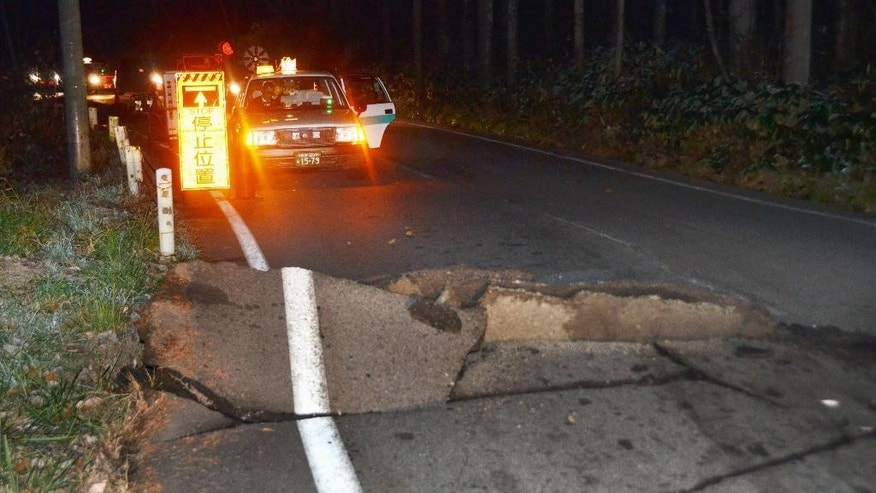 A taxi stops by a crack on the road that leads to Hakuba from Nagano, Nagano Prefecture, after a strong earthquake hit central Japan, Saturday, Nov. 22, 2014. The magnitude-6.8 earthquake struck in the mountainous area of central Japan Saturday night. No tsunami warning was issued. (AP Photo/Kyodo News) JAPAN OUT, CREDIT MANDATORY