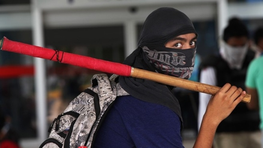 A masked student holds a stick during a protest against the disappearance, and probable murder, of 43 students in the state of Guerrero, at the Acapulco airport in Mexico, Monday, Nov. 10, 2014. Supporters of the missing students, refusing to believe they are dead, have kept up the protests that have blocked major highways and set government buildings ablaze in recent weeks. The 43 teachers-school students disappeared at the hands of a city police force on Sept. 26 in the town of Iguala. (AP Photo/Marco Ugarte)