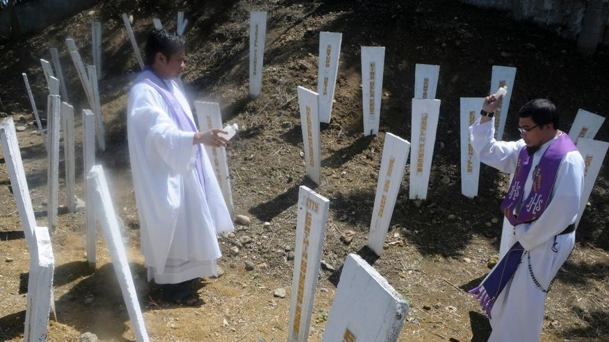 In this Nov. 21, 2014 photo, Roman Catholic priests bless the wooden markers at the site where 58 people, 32 of them journalists, were massacred at a remote village in  Ampatuan township, Maguindanao province in southern Philippines. Sunday Nov. 23, 2014 marks the fifth anniversary of the massacre, in Maguindanao, southern Philippines with the Ampatuan clan tagged as the prime suspects in the carnage. The massacre of 58 people is the country's worst election-related violence. (AP Photo/Bullit Marquez)