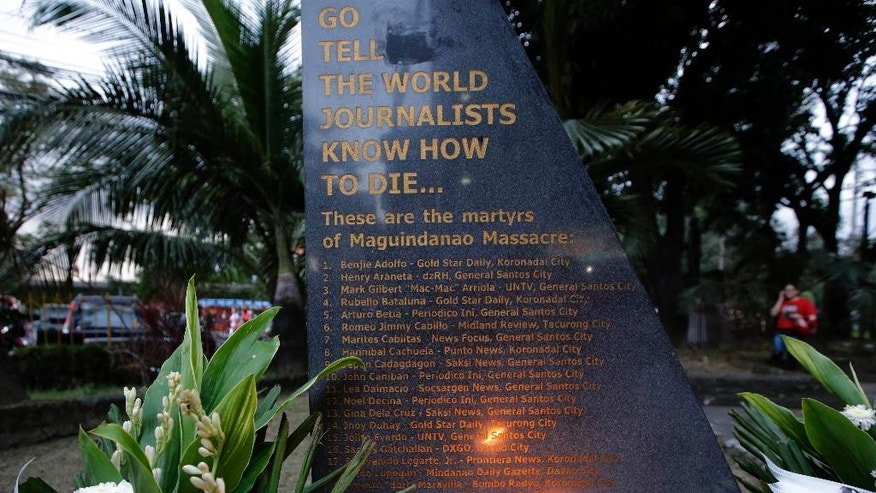 In this Nov. 21, 2014 photo, a lone candle lights up the granite marker engraved with the names of the 32 journalists, victims of a massacre in southern Philippines five years ago, outside the National Press Club in Manila, Philippines. Five years after gunmen flagged down a convoy of cars and massacred all 58 occupants, including scores of journalists, in a southern Philippine province, the body count continues to rise.  Just days before the Philippines marked Sunday, Nov. 23's anniversary of the carnage with prayers and calls to end impunity, another potential witness in the ongoing trial against the politically powerful suspects was gunned down. (AP Photo/Bullit Marquez)