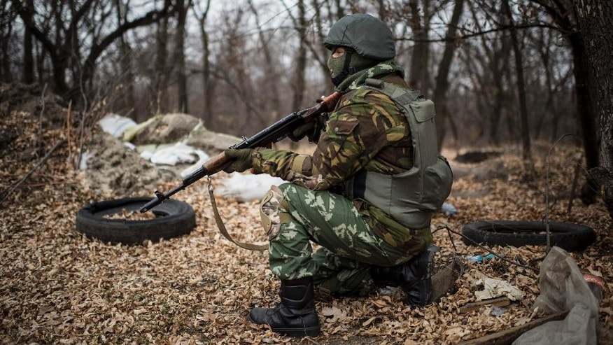 A Ukrainian serviceman gets ready to fire at his position next to a bridge over the river Siverskiy Donets, damaged by explosion during fighting between Pro-Russian rebels and Ukrainian government forces near Trehizbenka village, Luhansk region eastern Ukraine, Sunday, November. 23, 2014. More than 4,300 people have died in fighting in eastern Ukraine over the past half year, according to U.N. estimates. (AP Photo/Evgeniy Maloletka)