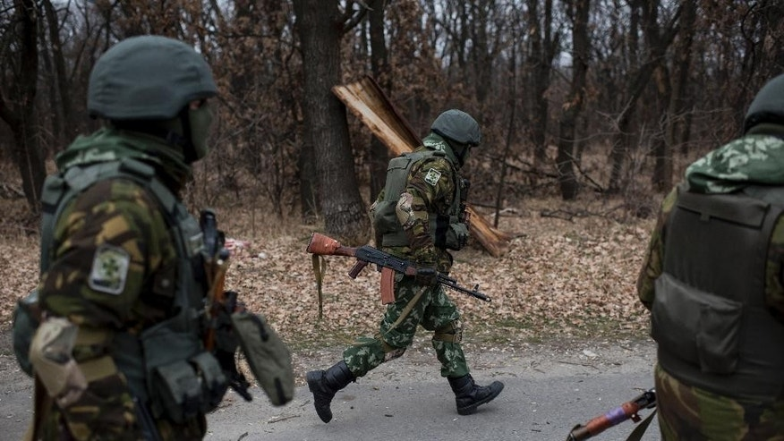 Ukrainian servicemen run to take their position next a bridge over the river Siverskiy Donets, damaged by explosion during fighting between Pro-Russian rebels and Ukrainian government forces near Trehizbenka village, Luhansk region eastern Ukraine, Sunday, November. 23, 2014. More than 4,300 people have died in fighting in eastern Ukraine over the past half year, according to U.N. estimates. (AP Photo/Evgeniy Maloletka)