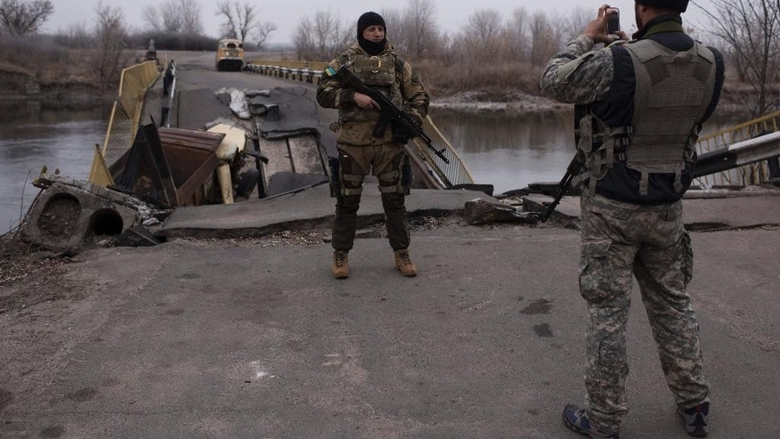 A Ukrainian serviceman takes a pictures of his comrade in front of a bridge over the river Siverskiy Donets, damaged by explosion during fighting between Pro-Russian rebels and Ukrainian government forces near Trehizbenka village, Luhansk region eastern Ukraine, Sunday, November. 23, 2014. More than 4,300 people have died in fighting in eastern Ukraine over the past half year, according to U.N. estimates. (AP Photo/Evgeniy Maloletka)