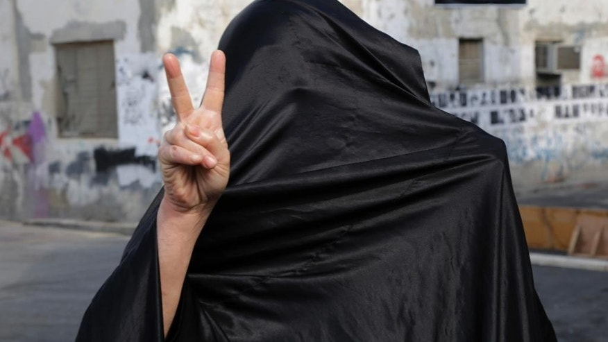 A Bahraini woman flashes a victory sign on a street where clashes occurred between police and anti-government protesters on a parliamentary election day in the Shiite neighborhood of Daih, Bahrain, Saturday, Nov. 22, 2014. Voters in Bahrain cast ballots Saturday in the island kingdom's first full parliamentary election since Arab Spring-inspired protests erupted four years ago, but a boycott called by the country's opposition threatens to overshadow the poll. (AP Photo/Hasan Jamali)