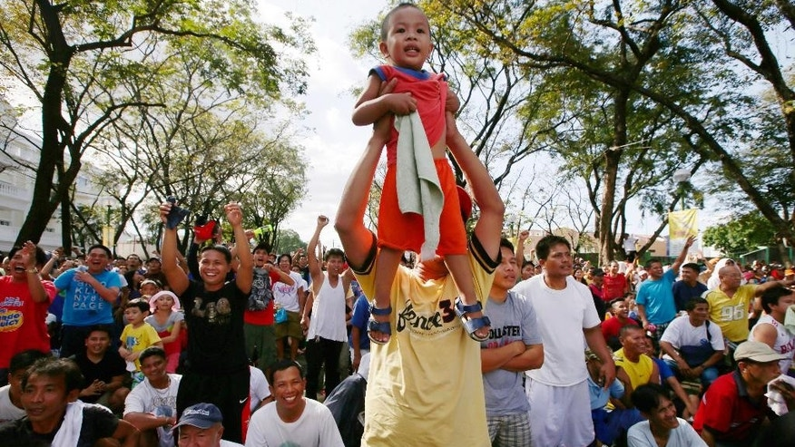 Rene Duhaylungsod raises his son Xian, 2, to cheer as hometown hero Manny Pacquiao fights opponent Chris Algieri, of the United States, in a live  broadcast from Macau, China, of their WBO welterweight title fight Sunday, Nov. 23, 2014 at suburban Marikina city, east of Manila, Philippines. Pacquiao, who floored Algieri six times in their 12-round fight, retained his crown via unanimous decision.(AP Photo/Bullit Marquez)