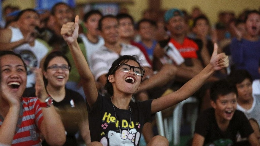 Filipinos react as they watch a free live satellite viewing of the WBO world welterweight title match between WBO welterweight champion Manny Pacquiao of the Philippines and WBO junior welterweight champion Chris Algieri of the U.S. in Macau,  at Camp Aguinaldo military headquarters in suburban Quezon city, north of Manila, Philippines on Sunday, Nov. 23, 2014. Pacquiao won the match. (AP Photo/Aaron Favila)