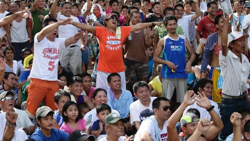 Filipinos cheer as hometown hero Manny Pacquiao fights his opponent Chris Algieri, of the United States, in a live broadcast from Macau, China, of their WBO welterweight title fight Sunday, Nov. 23, 2014 at suburban Marikina city, east of Manila, Philippines. Pacquiao, who floored Algieri six times in their 12-round fight, retained his crown via unanimous decision.(AP Photo/Bullit Marquez)