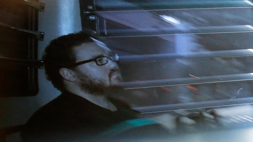 In this photo taken through a tinted glass, Rurik George Caton Jutting, a 29-years-old British banker, sitting in a prison bus arrives at a court in Hong Kong Monday, Nov. 24, 2014. The British banker is in his trial over the deaths of two Indonesian women he is suspected of killing. (AP Photo/Vincent Yu)