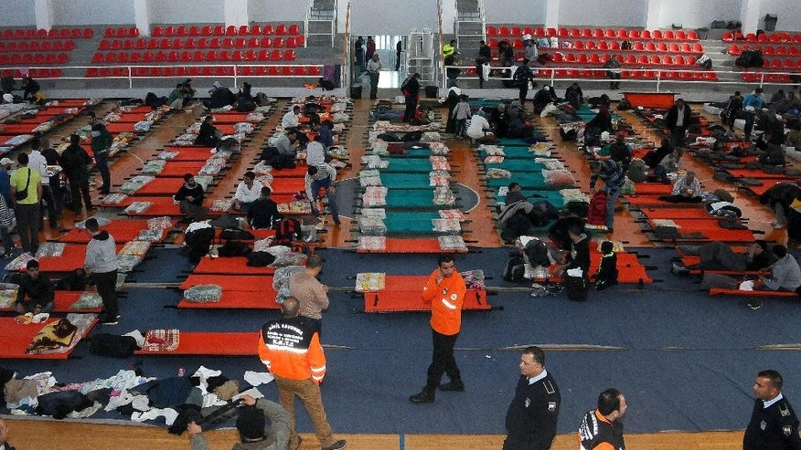 Migrants settle into a sports hall, after being rescued,  in the Turkish Cypriot breakaway northern coastal city of Kerynia or Girne, Sunday, Nov. 23, 2014. Over 200 migrants, apparently refugees from Syria, have been rescued after their damaged ship drifted for hours in rough seas off Cyprus' northern coast, an official said. (AP Photo/Nedim Enginsoy)