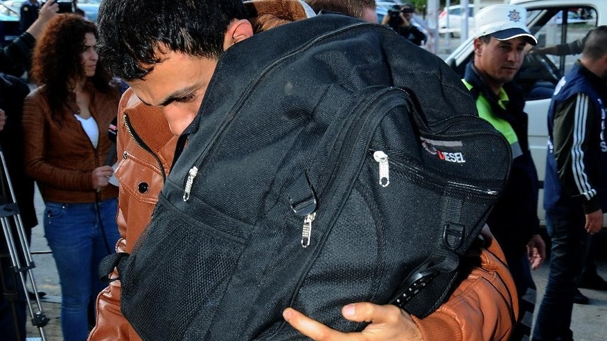 A migrant hold his bag after after being rescued, in the Turkish Cypriot breakaway northern coastal city of Kerynia or Girne, Sunday, Nov. 23, 2014. Over 200 migrants, apparently refugees from Syria, have been rescued after their damaged ship drifted for hours in rough seas off Cyprus' northern coast, an official said. (AP Photo/Nedim Enginsoy)