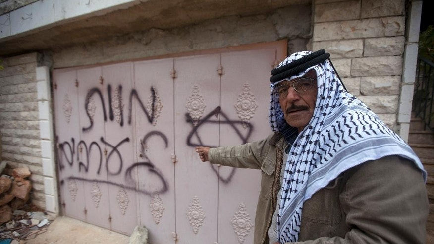 "A Palestinian man points to Hebrew graffiti reading ""Death to the Arabs"" following an arson attack in Khirbet Abu Falah, northeast of the West Bank city of Ramallah, Sunday, Nov. 23, 2014. The  family said their West Bank home was torched in an attack they blamed on Jewish settlers. Mohammed Abdelkarim, whose mother and sisters were inside the house when it was set alight, says Hebrew slogans were scrawled on the house. (AP Photo/Majdi Mohammed)"