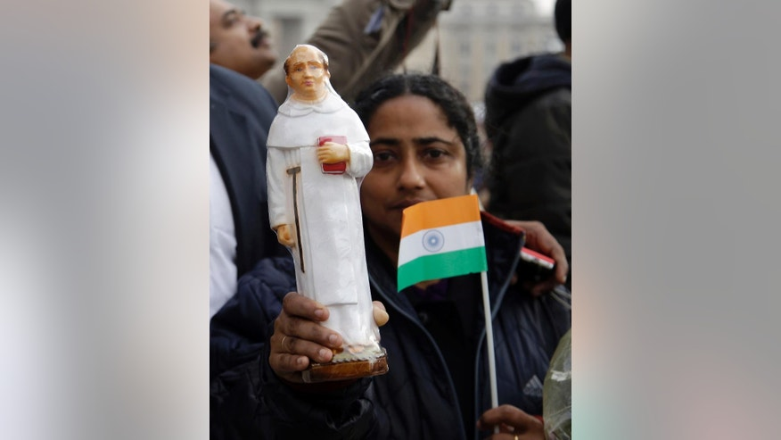 A faithful holds an Indian flag and a statuette of priest Elias Chavara prior to the start of a Canonization Mass celebrated by Pope Francis in St. Peter's Square, at the Vatican, Sunday, Nov. 23, 2014. (AP Photo/Gregorio Borgia)