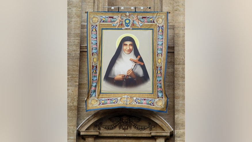 The tapestry of sister Eufrasia Eluvathingal is displayed on the St. Peter's Basilica prior to the start of her Canonization mass celebrated by Pope Francis in St. Peter's Square, at the Vatican, Sunday, Nov. 23, 2014. (AP Photo/Gregorio Borgia)