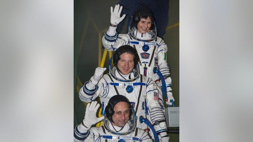 U.S. astronaut Terry Virts, centre, Russian cosmonaut Anton Shkaplerov, bottom, and Italian astronaut Samantha Cristoforetti, crew members of the mission to the International Space Station, ISS, gesture prior the launch of Soyuz-FG rocket at the Russian leased Baikonur cosmodrome, Kazakhstan, Monday, Nov. 24, 2014.  (AP Photo/Shamil Zhumatov, Pool)