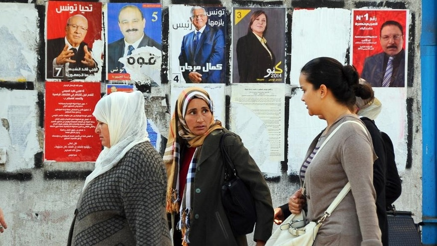 Tunisian women walk past a wall plastered with electoral campaign posters two days before the first round of the presidential elections in Tunis, Tunisia, Friday, Nov. 21, 2014. Tunisia's presidential election represents the final phase in a torturous and difficult transition to democracy since Tunisians overthrew Ben Ali in January 2011 — sparking the Arab Spring protests that ousted autocrats across the Middle East.  (AP Photo/Hassene Dridi)