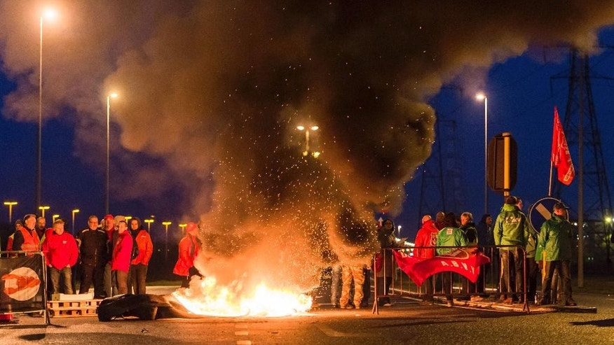 Workers burn tires to block one of the main entrances to the harbour in Antwerp, Belgium, during a first regional strike Monday, Nov. 24, 2014. (AP Photo/Geert Vanden Wijngaert)