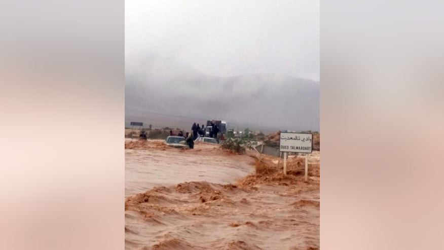 This image taken with a mobile phone shows residents of Guelmim, south western Morocco, standing on top of vehicles while stranded by rising waters, Monday, Nov. 24, 2014. Morocco's government reports that heavy flooding in the south has killed at least 17 people with another 18 missing after heavy rains over the weekend. In the southern city of Guelmim alone, 13 people were killed by a flash flood that roared through a dry river bed, reported the Interior Ministry in a statement carried by the national news agency late Sunday. (AP Photo)