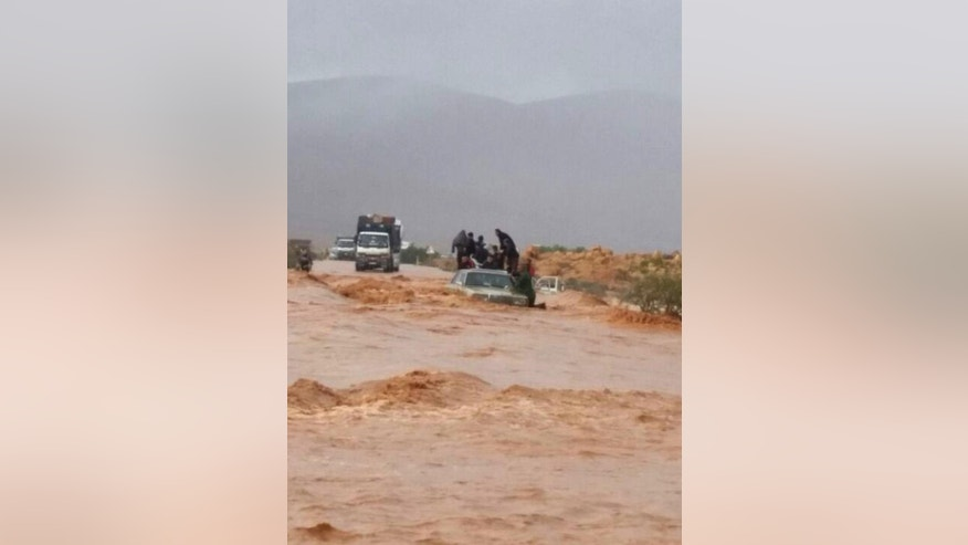 This image taken with a mobile phone shows residents of Guelmim, south western Morocco, standing on top of a vehicle while stranded by rising waters, Monday, Nov. 24, 2014. Morocco's government reports that heavy flooding in the south has killed at least 17 people with another 18 missing after heavy rains over the weekend. In the southern city of Guelmim alone, 13 people were killed by a flash flood that roared through a dry river bed, reported the Interior Ministry in a statement carried by the national news agency late Sunday. (AP Photo)