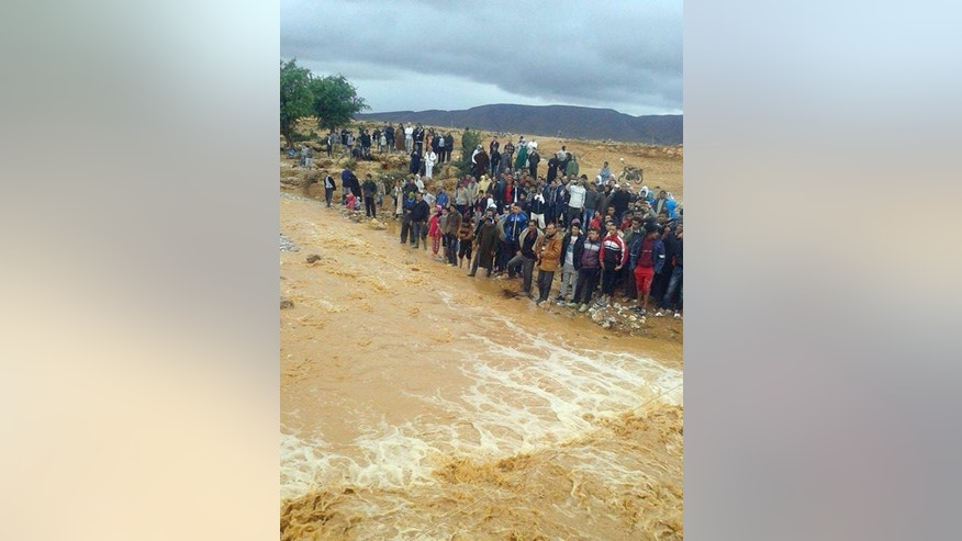 This image taken with a mobile phone shows residents of Guelmim, south western Morocco, watching the floodwaters, Monday, Nov. 24, 2014. Morocco's government reports that heavy flooding in the south has killed at least 17 people with another 18 missing after heavy rains over the weekend. In the southern city of Guelmim alone, 13 people were killed by a flash flood that roared through a dry river bed, reported the Interior Ministry in a statement carried by the national news agency late Sunday. (AP Photo)