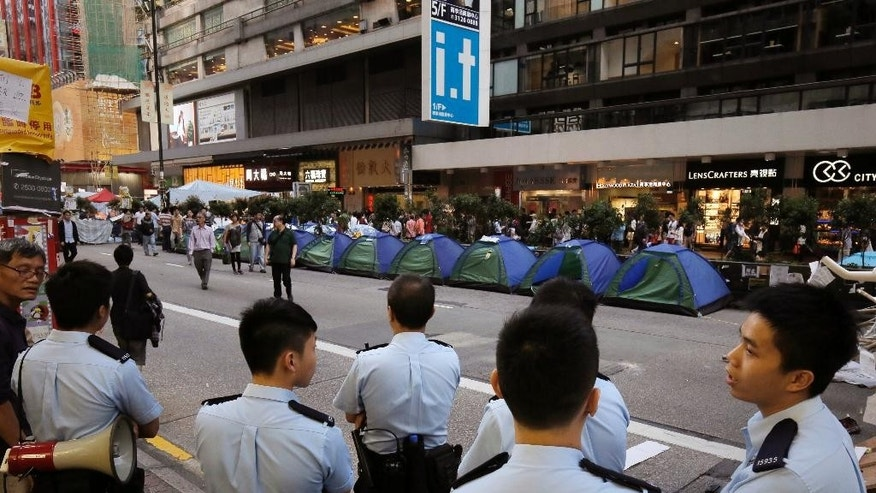 Police officers stand guard near tents set up by pro-democracy protesters in the occupied area of the Mong Kok district in Hong Kong Monday, Nov. 24, 2014. The student-led democracy protesters reject restrictions laid down by Beijing on inaugural 2017 elections for Hong Kong's top leader. But the students have been fighting to maintain momentum as the Hong Kong government appears to adopt a strategy of standing by in hopes it fizzles out. (AP Photo/Vincent Yu)