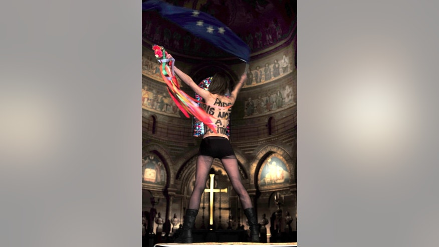 A member of the Ukrainian feminist protest group FEMEN, waves the European Union flag, as she stages a protest inside the cathedral of Strasbourg, eastern France, Monday, Nov. 24, 2014 against Tuesday's visit of the Pope to  Strasbourg . Pope Francis is set to deliver his first major speech on Europe with a holistic, if not holy, look at complex continental issues like joblessness and immigration. The pontiff's whirlwind, 4-hour visit Tuesday to the European Parliament and the Council of Europe, Europe's main human rights body, in Strasbourg is shaping up as more a secular stop than a liturgical layover. (AP/Photo Christian Lutz)