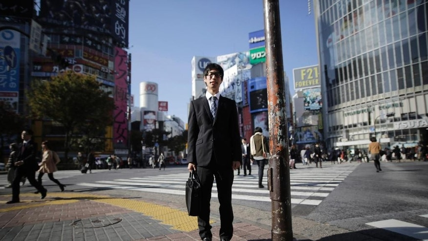 "In this Friday, Nov. 21, 2014 photo, Ryosuke Sunaga, a college senior, poses for a portrait at a scramble crossing at Shibuya shopping district in Tokyo. Japanese Prime Minister Shinzo Abe's choice last week to postpone a sales tax hike to help fend off recession comes less as a relief than as cause for greater concern over how the country will cope with its ballooning national debt. Sunaga is acutely aware that he'll be supporting an ever growing number of retirees throughout his future career. ""Speaking clearly, they just postponed it. In the end the tax will go up to 10%, to me it seems they are just using a temporary expedient and I don't really approve,"" Sunaga said. ""I don't really like the idea of higher taxes, but to a certain extent there is no avoiding passing the burden on to the younger generation. By the time I have kids the sales tax will probably be 15%, I'm thinking that will be tough. But compared to Europe the sales tax is still relatively low so raising it to 10% seems unavoidable to me."" (AP Photo/Eugene Hoshiko)"