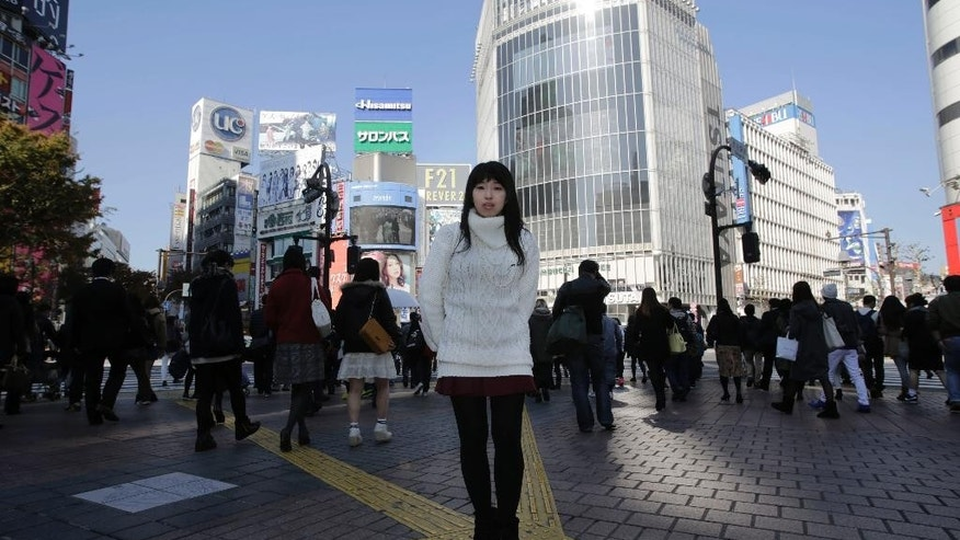 "In this Friday Nov. 21, 2014 photo, Kaori Endo, a 21-year-old bread factory worker from Ibaraki, north of Tokyo, poses for a portrait at a scramble crossing at Shibuya shopping district in Tokyo. Japanese Prime Minister Shinzo Abe's choice tlast week to postpone a sales tax hike to help fend off recession comes less as a relief than as cause for greater concern over how the country will cope with its ballooning national debt. Endo said she wouldn't mind paying more for taxes if she felt like she might benefit from them. But her bigger concern is getting a permanent job. ""Right now I'm living with my family but I'm thinking about how I will support my parents,"" she said. Endo is hoping the government will be able to handle its growing debt and other problems. ""I want to be hopeful,"" she said. ""This is the country I was born in so I want to believe in it."" (AP Photo/Eugene Hoshiko)"