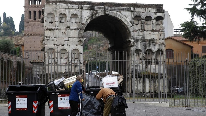 In this photo taken in Rome on Nov. 6 2014, people search through rubbish in front of the Giano Arch in downtown Rome. Ignazio Marino promised to bring order to Rome's chaos when he was elected mayor in a landslide in June last year. Instead, critics say the liver transplant surgeon is the affliction not the cure, and are pressuring him to resign. (AP Photo/Gregorio Borgia)
