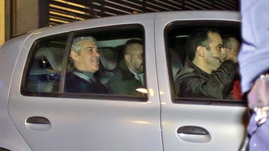 Portugal's former Prime Minister Jose Socrates, in the back seat of the car on the left, leaves a court in a Portuguese police car after being questioned, in Lisbon, Sunday, Nov. 23, 2014. Jose Socrates is spending a third straight night in jail as officials continue to investigate him for suspected corruption, money-laundering and tax fraud. (AP Photo/Francisco Seco)
