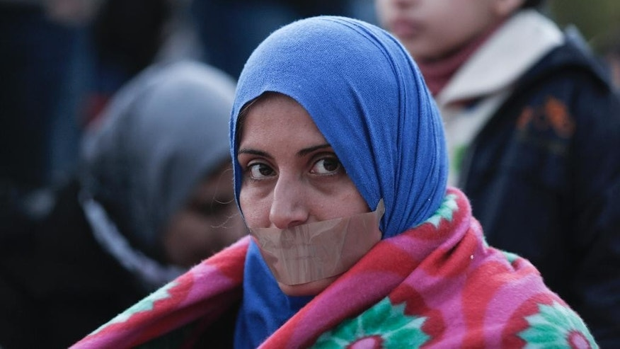 A Syrian protester sits with her mouth taped shut, during a protest outside parliament in central Athens, on Monday, Nov. 24, 2014. About 150 Syrian civil war refugees started a hunger strike Monday, urging Greece's government to grant them full refugee status. (AP Photo/Petros Giannakouris)