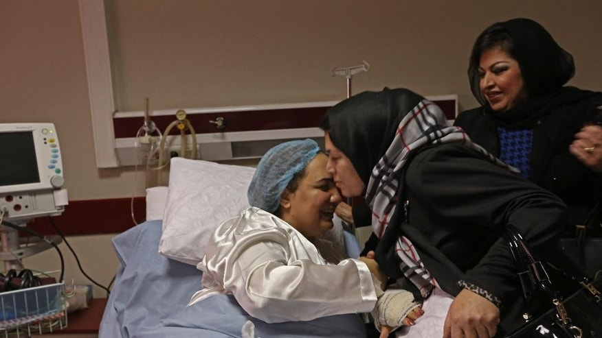 In this photo taken Sunday, Nov. 23, 2014, a visitor kisses Afghan lawmaker Shukria Barakzai at a government hospital she was taken into after a suicide attack last week in Kabul, Afghanistan. Attacks in the capital Kabul have escalated since President Ashraf Ghani took office in September. Insurgent groups oppose the bilateral security agreement he signed with Washington, ratified by Parliament on Sunday, as well as his support for women's rights and peace talks with the Taliban. (AP Photo/Rahmat Gul)