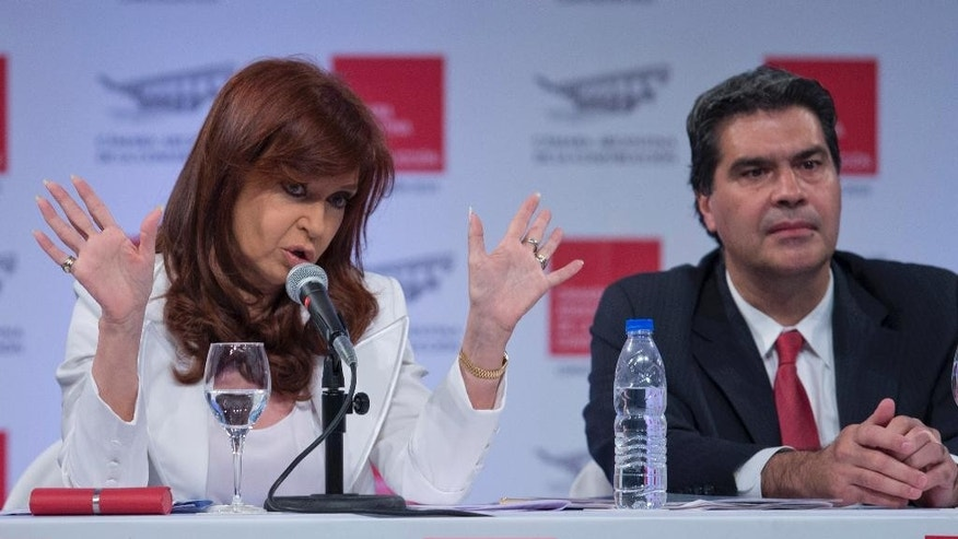 Argentina's President Cristina Fernandez, left, talks next to Argentina's Cabinet Chief Jorge Capitanich, during the Argentine Chamber of Construction annual convention in Buenos Aires, Argentina, Tuesday, Nov. 25, 2014. Fernandez appeared for the first time in public after more than 20 days, after recovering of a bacterial infection. (AP Photo/Natacha Pisarenko)