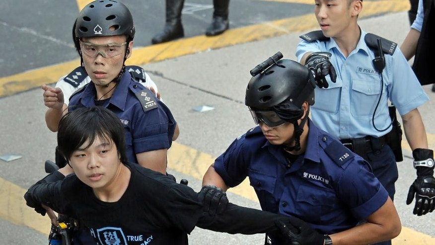 A pro-democracy protester is taken away by police officers as workers start clearing away barricades at an occupied area in Mong Kok district of Hong Kong Tuesday, Nov. 25, 2014. Hong Kong authorities on Tuesday began clearing away some barricades from part of the pro-democracy protest site, scene of previous violent confrontations with police and angry mobs. (AP Photo/Vincent Yu)