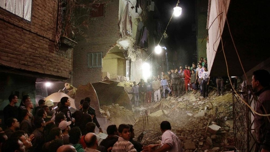 Rescue workers and civilians search for survivors in the rubble of an eight-story building that collapsed in the Cairo suburb of Matariya, early Tuesday, Nov. 25, 2014. Police officials say several people were killed. Building collapses are common in Egypt, where shoddy construction is widespread in shantytowns, poor city neighbourhoods and rural areas. (AP Photo Ahmed Abdel Fattah, El Shrouk Newspaper) EGYPT OUT