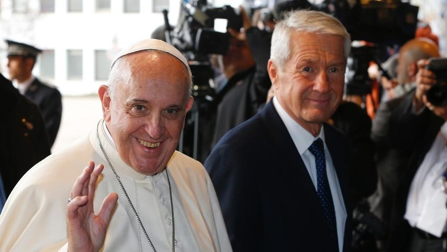 Pope Francis waves as he arrives with Secretary General Thorbjoern Jagland, right, at the Council of Europe in Strasbourg, Tuesday, Nov. 25, 2014. (AP P hoto/Yves Herman, Pool)