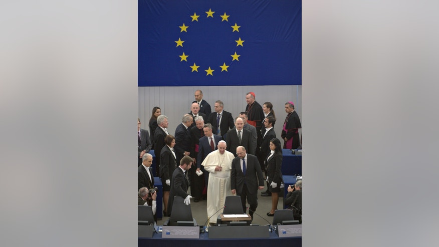 In this photo provided by Vatican newspaper L'Osservatore Romano, Pope Francis, center, is flanked by President of the European Parliament Martin Schulz, second from right, at the European Parliament in Strasbourg, France, Tuesday, Nov. 25, 2014. Pope Francis has demanded Europe craft a unified and fair immigration policy, saying the thousands of refugees coming ashore need acceptance and assistance, not self-interested policies that risk lives and fuel social conflict. Francis made the comments Tuesday to the European Parliament during a brief visit meant to highlight his vision for Europe a quarter-century after St. John Paul II travelled to Strasbourg to address a continent still divided by the Iron Curtain. (AP Photo/L'Osservatore Romano)