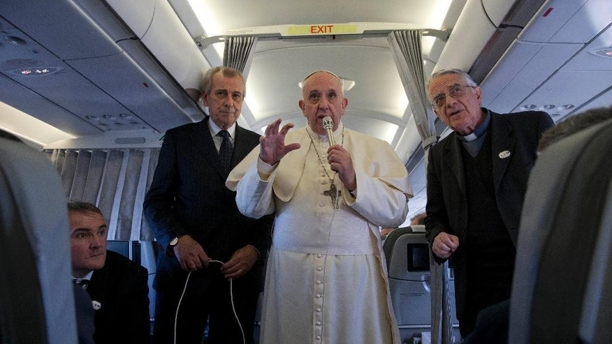 Pope Francis, flanked by Vatican spokesman father Federico Lombardi, first right, talks to journalists during a press conference he held aboard the papal flight on his way back from Strasbourg, eastern France, at the end of a one day visit to the European Parliament and Council, Tuesday, Nov. 25, 2014. Pope Francis has demanded Europe craft a unified and fair immigration policy, saying the thousands of refugees coming ashore need acceptance and assistance, not self-interested policies that risk lives and fuel social conflict. Francis made the comments Tuesday to the European Parliament during a brief visit meant to highlight his vision for Europe a quarter-century after St. John Paul II travelled to Strasbourg to address a continent still divided by the Iron Curtain. (AP Photo/Andrew Medichini)