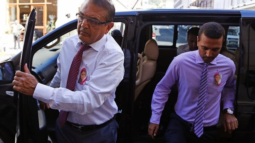 Vinod Hindocha, left, the father of slain Anni Dewani,  arrives at the high court in the city of Cape Town, South Africa, Tuesday, Nov. 25, 2014. British businessman and accused murder suspect Shrien Dewani is charged with orchestrating the murder of his wife, Anni, while the newly-married couple were on honeymoon in South Africa in 2010. (AP Photo/Schalk van Zuydam)