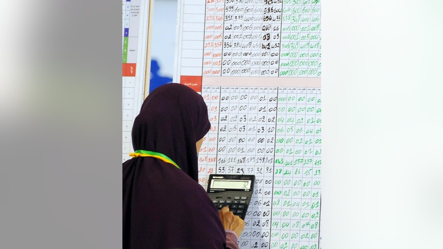 An election official uses a calculator to count votes displayed on a board at a polling station in Tunis, Tunisia, Monday, Nov. 24, 2014. A veteran politician from the previous regime that ran on a platform of restoring the prestige of the state took the lead in Tunisia's first free and fair presidential election Sunday, according to exit polls. But there will still likely be a runoff next month. (AP Photo/Hassene Dridi)