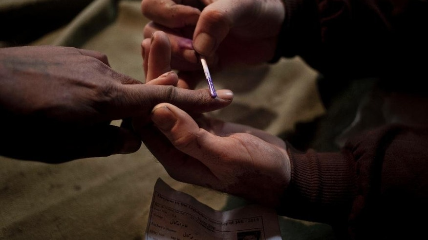 A polling officer, right, puts an ink mark  on the finger of a voter during the first phase of voting to the Jammu and Kashmir state assembly elections in  Khranihama, some 25 kilometers (16 miles) north east of Srinagar, Indian controlled Kashmir, Tuesday, Nov. 25, 2014. Thousands lined up to cast their votes amid a boycott call by Muslim separatist groups who reject India's sovereignty over the disputed Himalayan region. (AP Photo/ Dar Yasin)