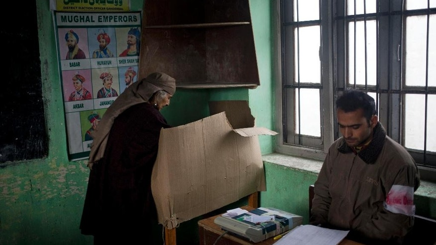 An elderly Kashmiri woman casts her vote at a polling station set up inside a school during the first phase of voting to the Jammu and Kashmir state assembly elections in Ganderbal, about 20 kilometers (12 miles) north east of Srinagar, Indian controlled Kashmir, Tuesday, Nov. 25, 2014. Thousands lined up to cast their votes amid a boycott call by Muslim separatist groups who reject India's sovereignty over the disputed Himalayan region. (AP Photo/ Dar Yasin)