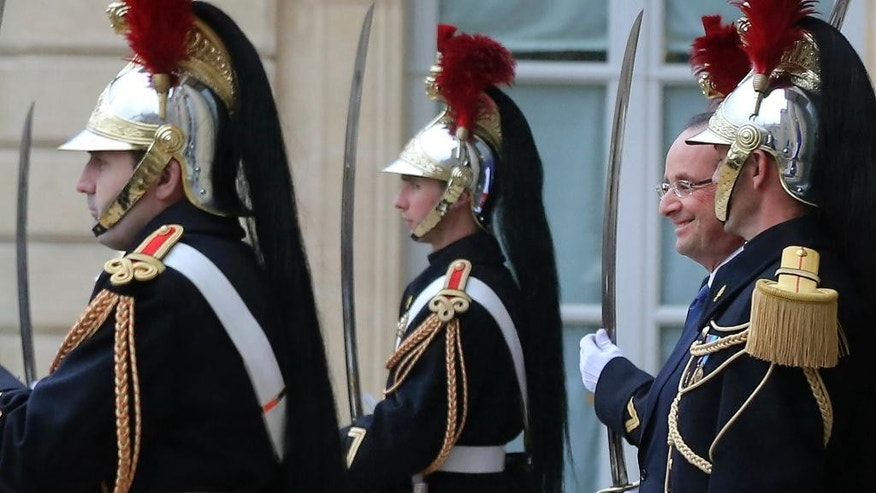 FILE - - In this Tuesday Nov. 12 2013 file photo, France's President Francois Hollande, right, stands among honor guards as he awaits head of states for a meeting on youth unemployment in the European Union at the Elysee Palace in Paris. This image won the 2013 Photography Elysee award for Associated Press photographer Michel Euler. (AP Photo/Michel Euler, File)