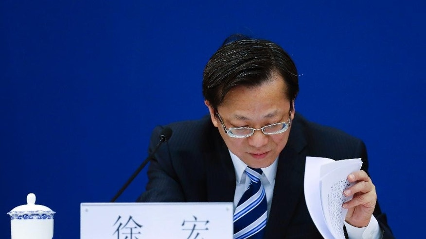 Xu Rong, director-general of the treaty and law division for China's Foreign Ministry looks at documents during a press conference at the Ministry of Foreign Affairs office in Beijing Wednesday, Nov. 26, 2014. Xu calling on the U.S. and other Western countries to put aside their wariness of China's justice system and work with Beijing to send back officials who have absconded overseas with ill-gained loot. (AP Photo/Andy Wong)