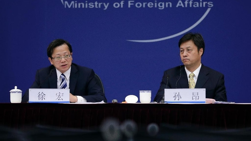 Xu Rong, director-general of the treaty and law division for China's Foreign Ministry, left, speaks next to Sun Ang, Special Coordinator for Fugitive Repatriation and International Law Enforcement Cooperation for China's Foreign Ministry during a press conference at the Ministry of Foreign Affairs office in Beijing Wednesday, Nov. 26, 2014. Xu calling on the U.S. and other Western countries to put aside their wariness of China's justice system and work with Beijing to send back officials who have absconded overseas with ill-gained loot. (AP Photo/Andy Wong)